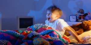 Boy (5-7) screaming at shadows of monsters on wall